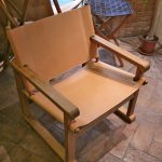 Squat armchair in natural leather and wood